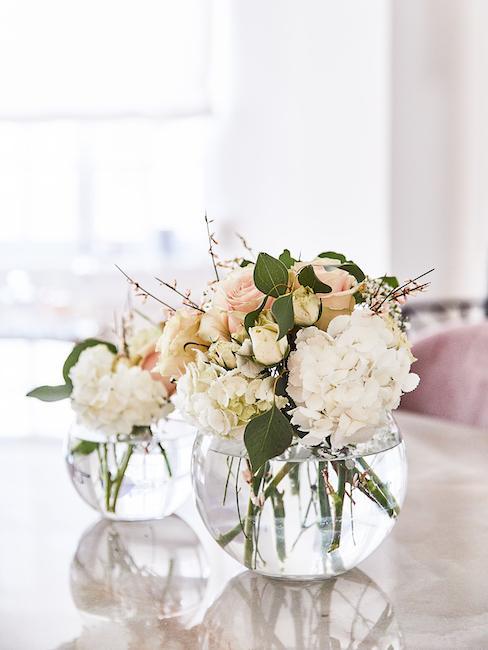 Fleurs pastel dans un vase boule transparent sur table en marbre beige