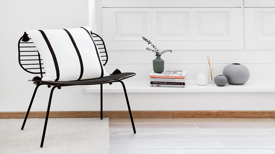 Schwarzer Stuhl mit gestreiften Kissen und Deko