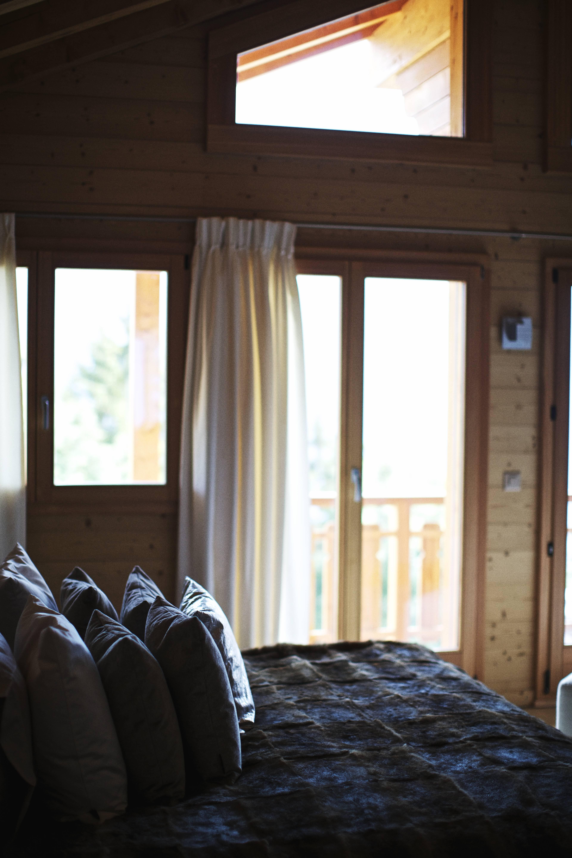 Una camera da letto Chalet Style non rinuncia ad un risveglio di luce. Quindi, sì a grandi finestre incorniciate da tende in tessuti leggeri, che non appesantiscano l'ambiente e non esercitino un'azione troppo oscurante rispetto ai raggi del sole del mattino.