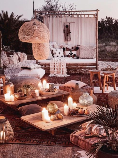 Giardino in stile boho con candele, poltrone con cuscini chiari e tavolini in legno