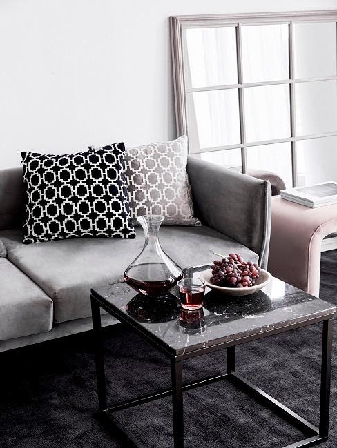 Couchtisch mit Rotwein-Karaffe und Trauben vor einer Couch