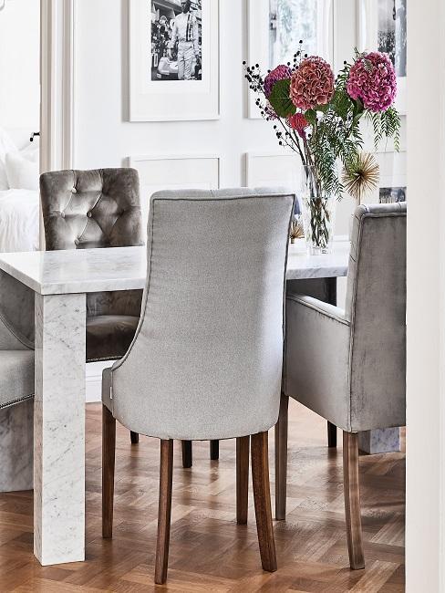 Esszimmer mit Marmortisch und edlen Samtstühlen in Grau