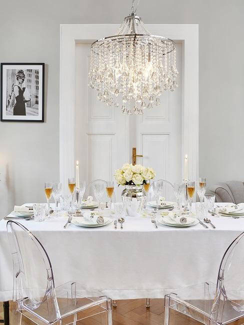 Helles Esszimmer mit dedecktem Tisch, transparenten Luxus Kartell Stühlen und einem opulenten Kronleuchter