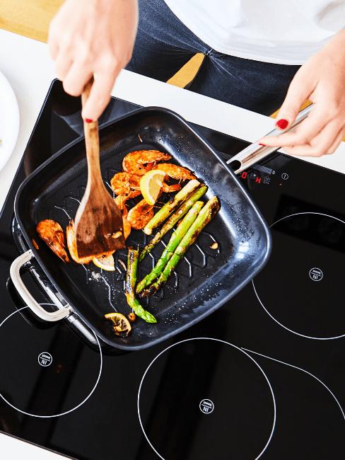 Piano cottura a induzione con padella e verdure