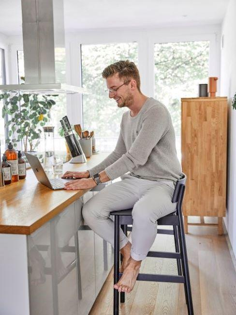 uomo che lavora al computer seduto al bancone della cucina