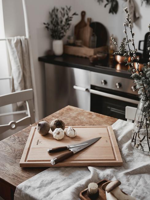 Drewniany stół w kuchni na któym leży deska do krojenia