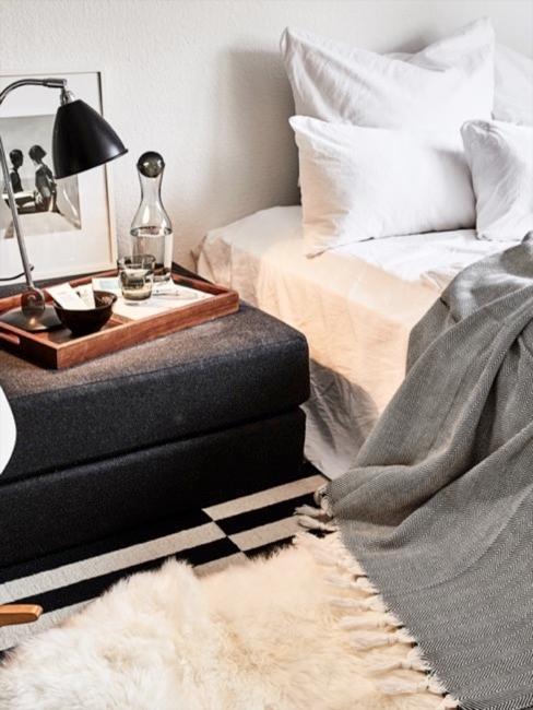 Białe łóżko z antracytowym stolikiem nocnym, drewnianą tacą i czarną lampką nocną.