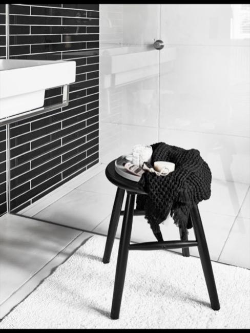 Salle de bain carrelée blanche avec carrelage mural noir et tabouret noir au premier plan