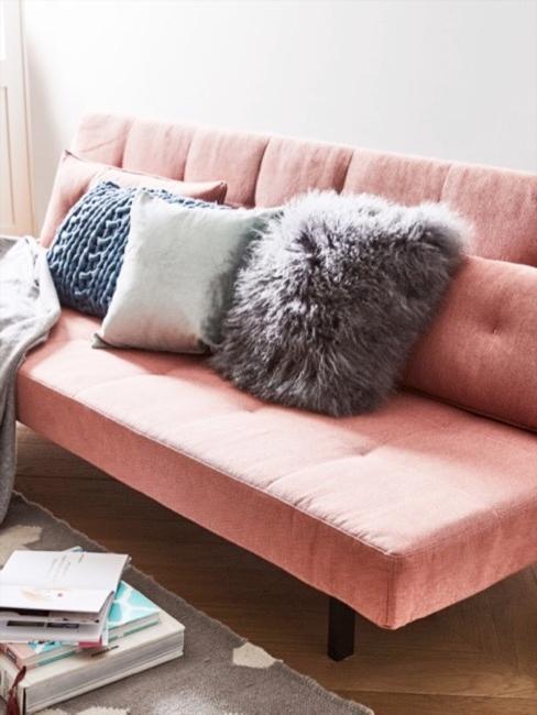 Różowa sofa futon z dekoracyjnymi poduszkami