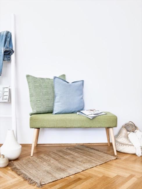 banc vert décoré des coussins devantun mur clair