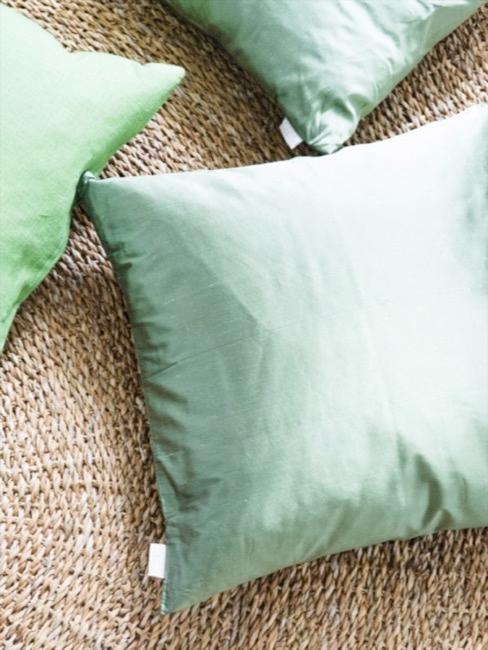 Cojines en color verde greenery sobre puf de mimbre