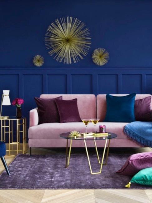 Pokój z kobaltowo-niebieską ścianą, różową sofą i poduszkami w odcieniach błękitu i fioletu