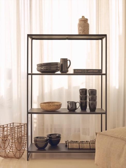 Estantería negra con cuencos y vasos de cerámica y cortinas beige