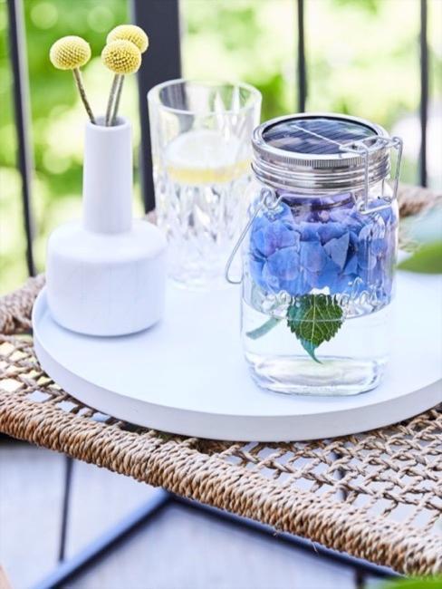 Mesa de exterior con jarrón de flores y vaso de agua sobre bandeja blanca