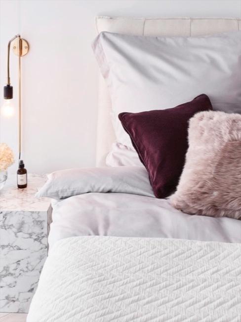 Łożko z białą pościelą i fioletowymi poduszkami