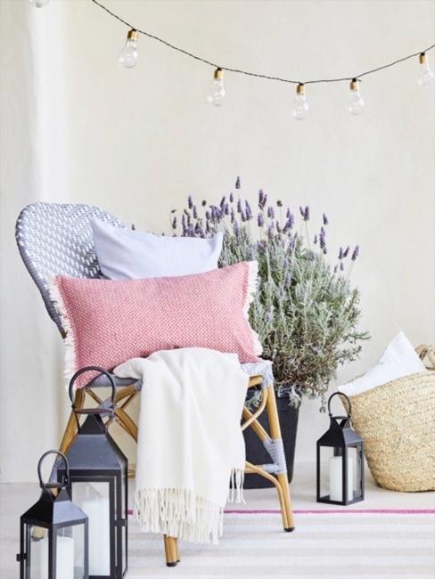 coin cosy sur la petite terrasse avec une chaise, coussins et plaid, paniers, lanterne et un pot de lavande