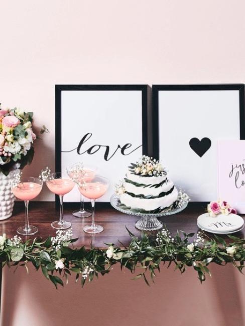 Torcik weselny na udekorowanym stole obok kieliszków z szampanem