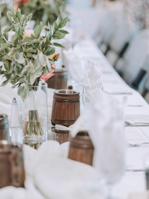 Stół weselny ozdobiony kwiatami i dekoracjami w naturalnych odcieniach