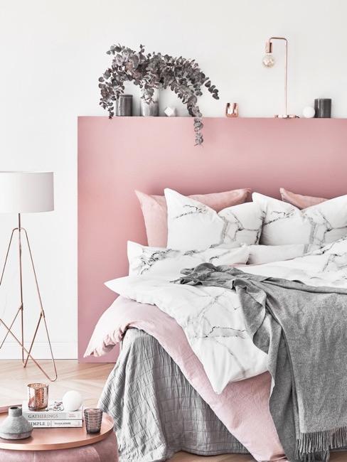 Dormitorio rosa con mantas grises y rosas