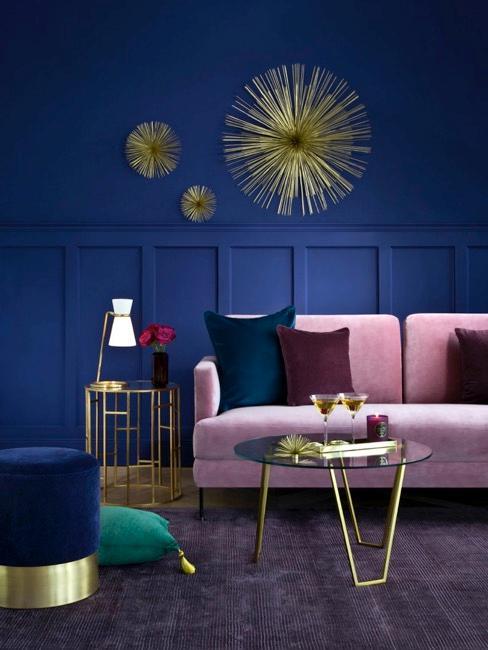 Niebiesko fioletowy salon z metalowymi dekoracjami ściennymi i różową sofą