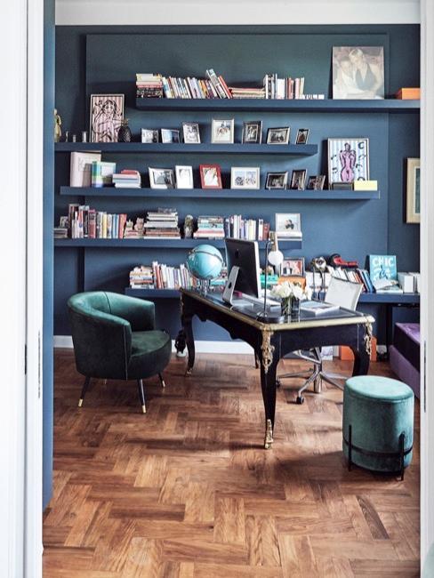 Una oficina con paredes y muebles de colores oscuros y con estantes