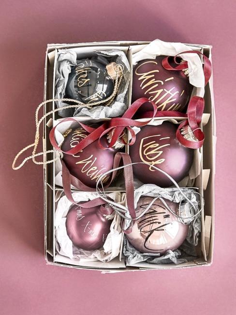 Różowe bombki ze złotymi napisami spakowane w pudełku