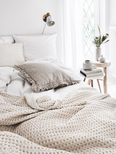 Zbliżenie na łóżko z pościelą i narzutą na łóżko w naturalnych barwach