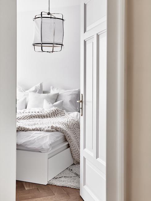 Sypialnia w jasnych barwach z wiszącą lampą i narzutą na łóżku