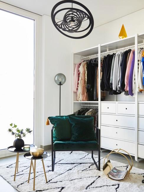 armario con ropa y un sillón verde
