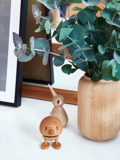 Deux figurines en bois avec plante dans un vase en bois