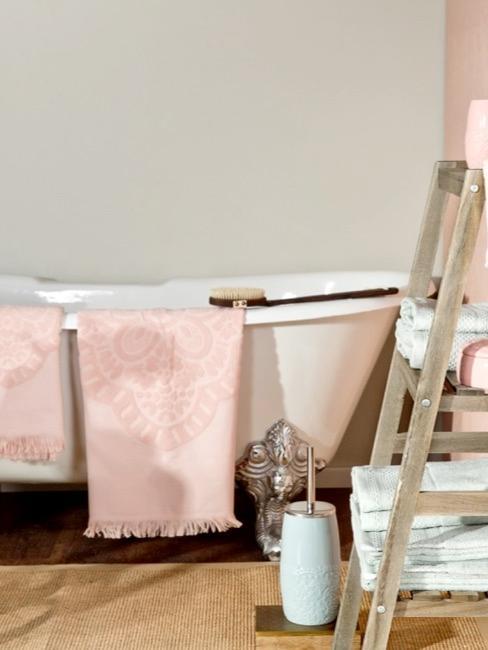 cuarto de baño con bañera blanca, una escalera y toallas rosas
