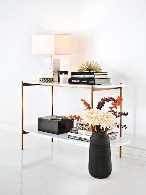 Estantería con libros decorativos, lámpara blanca de mesa y jarrón negro con flores