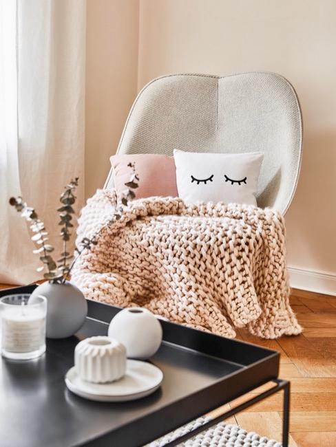 Manta chinky knit sobre sofa beig y cojines coloridos