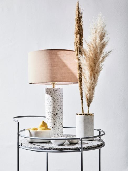 Dekoracyjny stolik z lampą, małymi miseczkami oraz elementami dekoracyjnymi