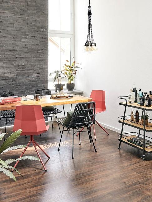Table en bois brut dans une salle à manger moderne, couleurs des chaises vert foncé et rouge / orange, mur en brique grise et desserte