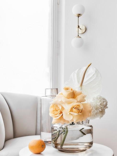 Weißes Calla Blumenbouquet in durchsichtiger Vase auf Marmortisch