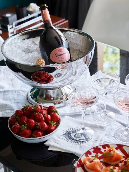 Table à manger avec bouteille de vin refroidie dans la glace et bol avec fraises