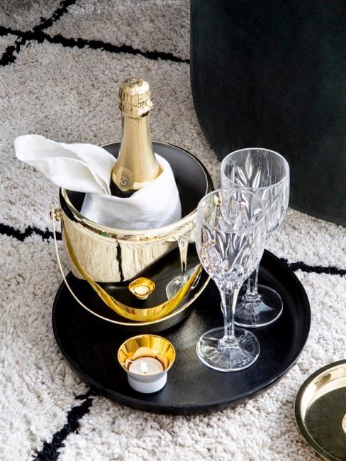 Refroidisseur doré sur plateau noir et deux verres de vin