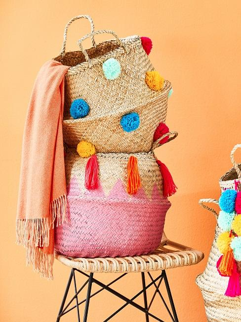 Paniers décorés des houppes et des pompons colorés posés sur une chaise et une couverture en orange fluo