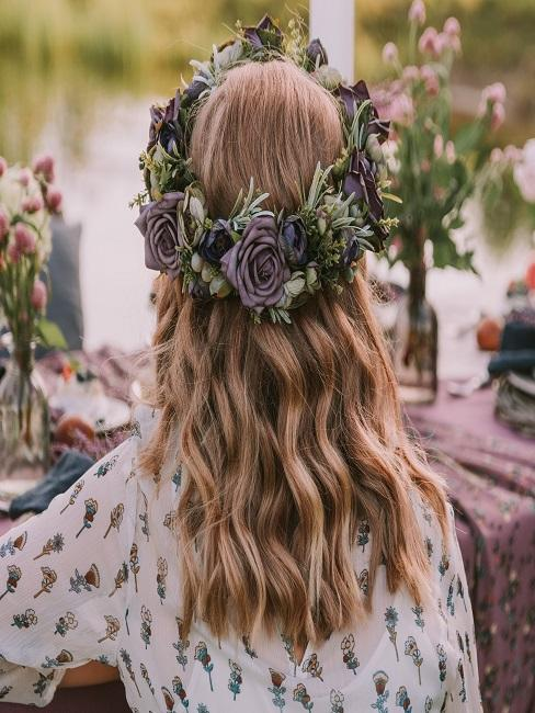 Frau mit Blumenkranz im Haar von hinten an einem Tisch sitzend