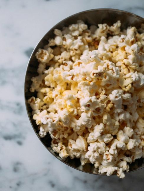Popcorn w misce na marmurowym blacie jako przekąska na wieczór filmowy