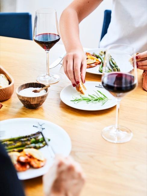 Rotweingläser auf Esstisch mit zwei speisenden Personen