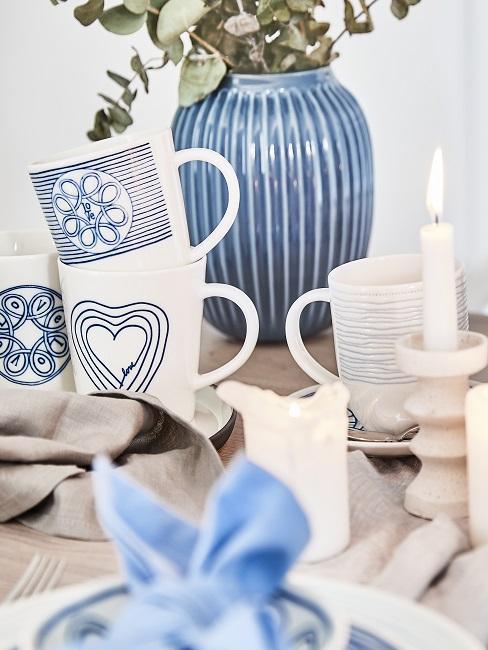 decoración de mesa con cerámica, jarrón y velas de color blanco y azul