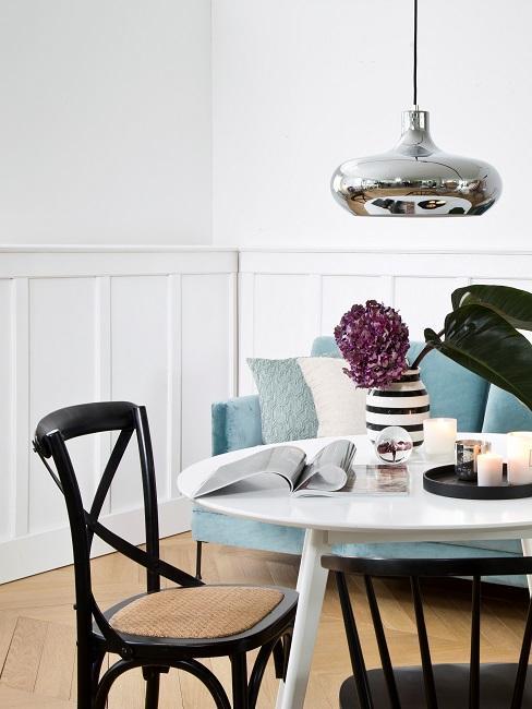Une table ronde en blanc, à côté d'une chaise noire avec assise en cannage à l'arrière-plan un canapé bleu.