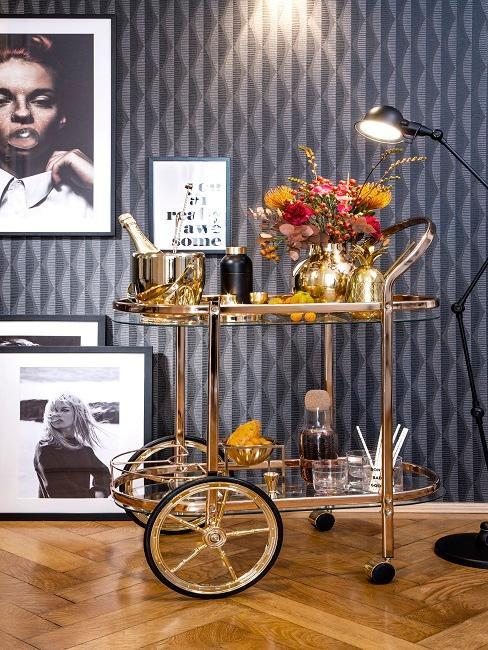 Wózek barowy w salonie z dużą ilością dekoracji przed ścianą z tapetą w stylu retro.