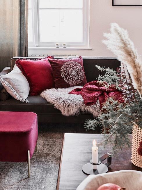 Sofa z poduszkami i kocem w kolorze bordowym obok bordowego pufa