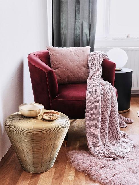 Bordowy fotel z poduszką i kocem w odcieniach różu obok złotego stolika