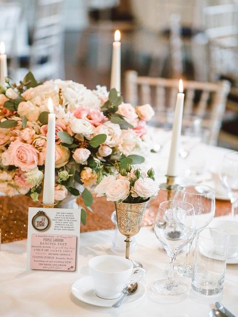 Gedeckter Tisch mit klassischen Kerzen und Blumendeko in Rosa