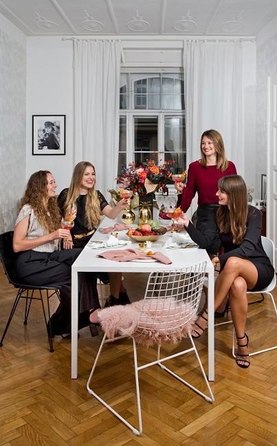 Gedeckter Tisch mit Deko in einem Wohnzimmer, daran sitzen vier Frauen mit Drinks