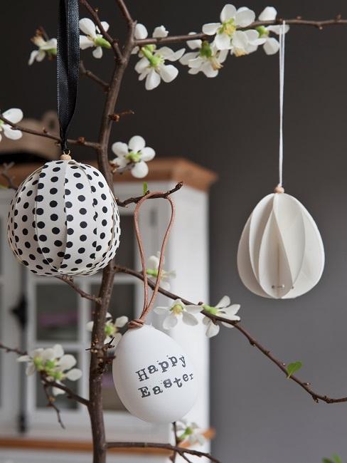 Bemalte Ostereier hängen an einem Dekoast im Essraum.